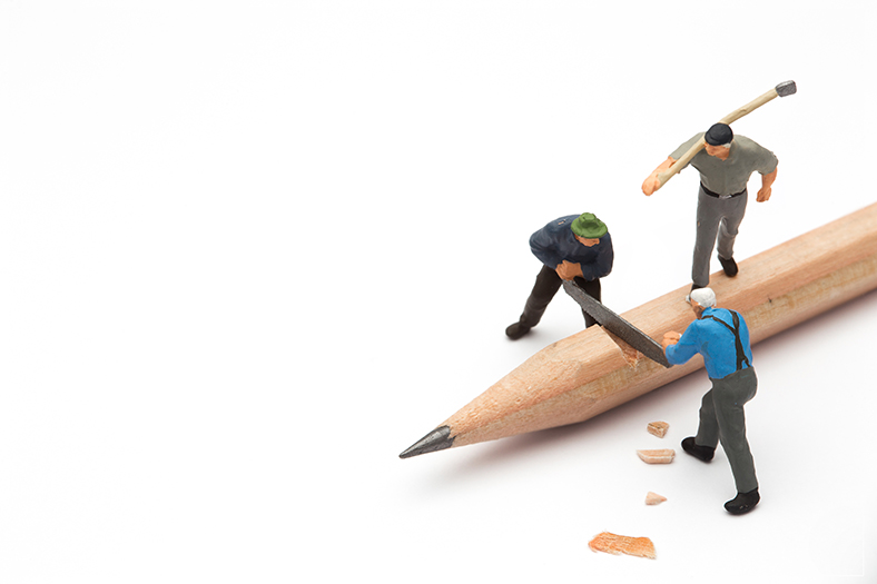 Mini people cutting pencil